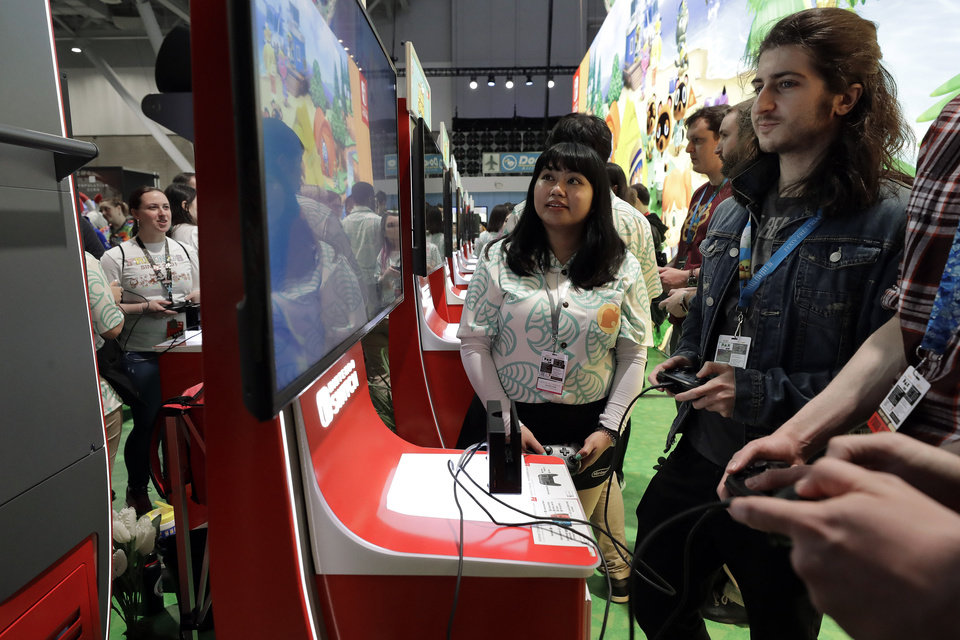 Photo -  Visitors to the Pax East conference play the new Nintendo Switch video game Animal Crossing on Feb. 27 in Boston. [associated press file photo]