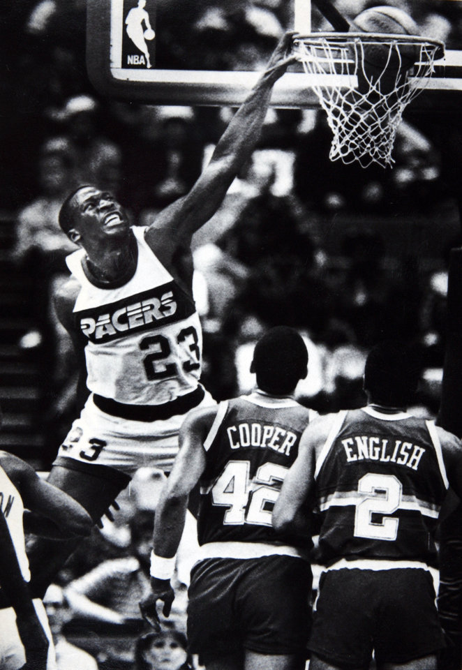 Photo - Former OU basketball player Wayman Tisdale. Indiana Pacers forward Wayman Tisdale slams the ball through the hoop over Denver's Wayne Cooper and Alex English Wednesday night. Photo taken, Photo published 12/6/85 in The Daily Oklahoman. ORG XMIT: KOD
