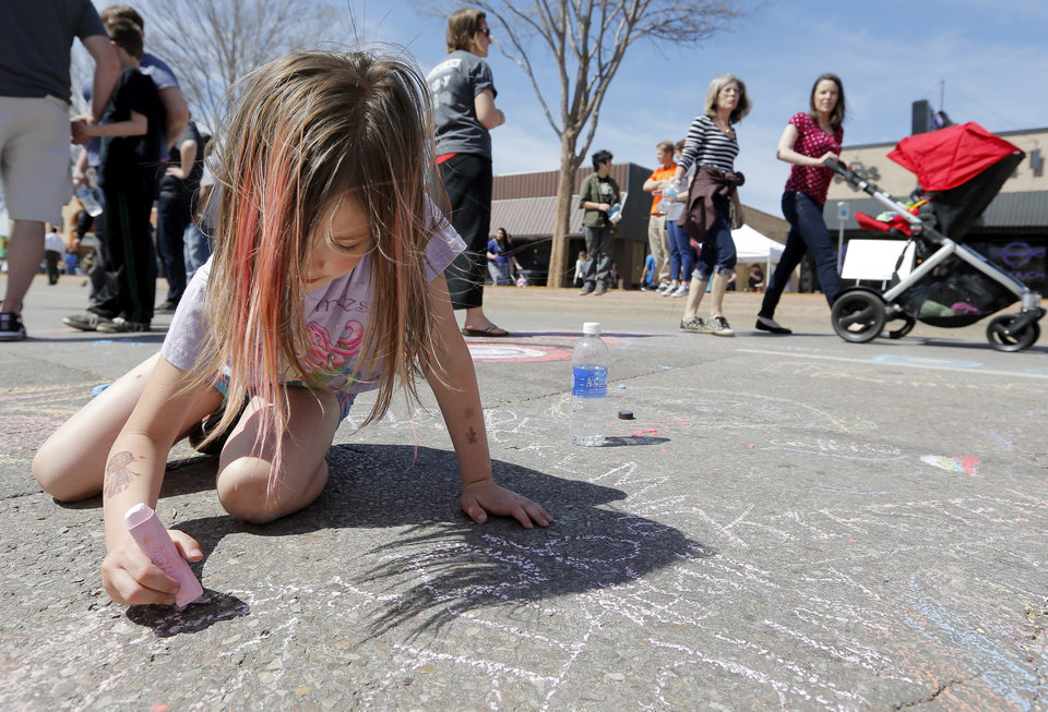 Photo - Nicole Fairchild, 6, draws on the street with chalk during the Open Streets OKC event along NW 23rd St. in Oklahoma City, Sunday, March 30, 2014. From noon until 4pm, NW 23rd St. between Robinson and Western was closed to cars for the event. Photo by Nate Billings, The Oklahoman