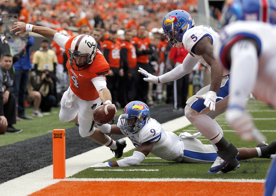 Photo - Oklahoma State's J.W. Walsh (4) scores a touchdown in front of Kansas Fish Smithson (9) and Marcquis Roberts (5)  during a college football game between the Oklahoma State University Cowboys (OSU) and the Kansas Jayhawks (KU) at Boone Pickens Stadium in Stillwater, Okla., Saturday, Oct. 24, 2015. Photo by Sarah Phipps, The Oklahoman