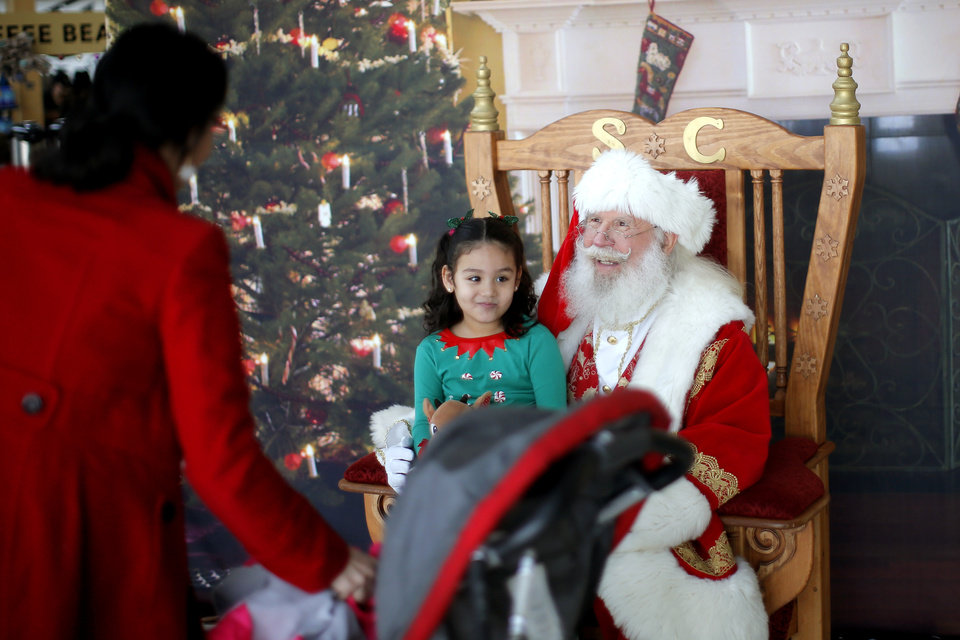 Photo -  Santa Claus visits with 4-year-old Amy Mendoza and her mother, Lucy Mendoza, of Norman on Tuesday inside Will Rogers World Airport. [Photo by Bryan Terry, The Oklahoman]