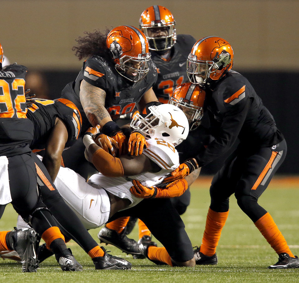Photo - A host of Oklahoma State defenders tackle Malcolm Brown (28) during the college football game between the Oklahoma State University Cowboys (OSU) the University of Texas Longhorns (UT) at Boone Pickens Staduim in Stillwater, Okla. on Saturday, Nov. 15, 2014.  Photo by Sarah Phipps, The Oklahoman