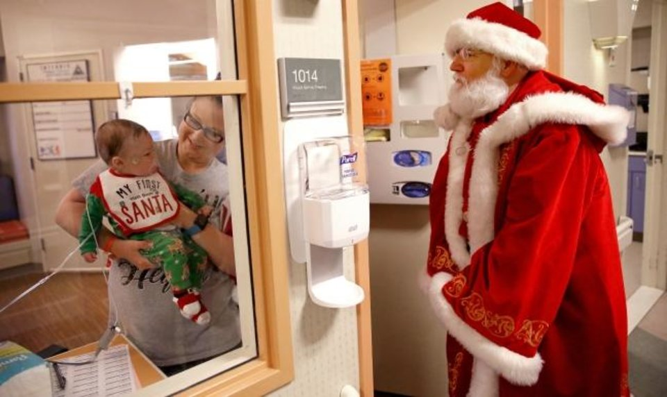Photo -  Santa Claus visits Briggs Cole, 4 months, and his mom Katy Cole on Christmas Eve at Integris Children´s at Baptist Medical Center.   [Sarah Phipps/The Oklahoman]