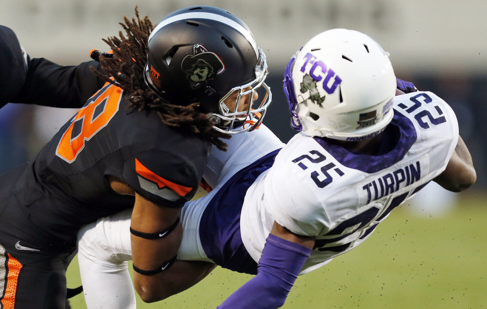 Photo - Oklahoma State's Ramon Richards (18) stops TCU's KaVontae Turpin (25) during the college football game between the Oklahoma State Cowboys (OSU) and TCU Horned Frogs at Boone Pickens Stadium in Stillwater, Okla., Saturday, Nov. 7, 2015. OSU won 49-29. Photo by Nate Billings, The Oklahoman