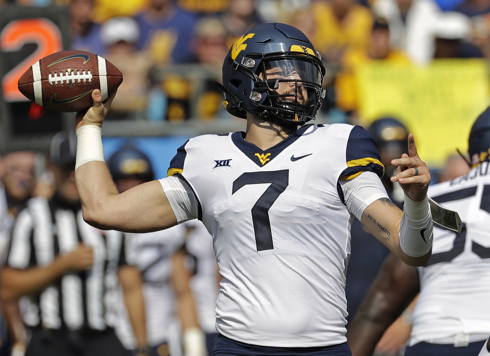 Photo - FILE - In this Sept. 1, 2018 file photo, West Virginia's Will Grier (7) looks to pass against Tennessee in the first half of an NCAA college football game in Charlotte, N.C. Oklahoma's Kyler Murray, West Virginia's Will Grier, Iowa State's Brock Purdy and Sam Ehlinger of Texas have been impressive and could determine which teams makes it to the Dec. 1 title game in Arlington, Texas. (AP Photo/Chuck Burton, File)