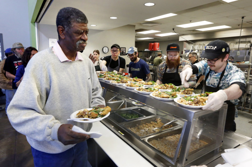 Photo -  Larry Tillman is served as Nonesuch Chef Colin Stringer leads his group of ambitious chefs to create a one-of-a-kind lunch for clients of the Homeless Alliance in Oklahoma City. [Photo by Steve Sisney, The Oklahoman]