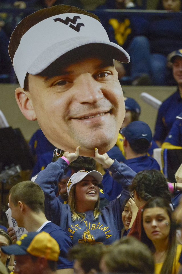 Photo -  A Mountaineers fan holds aloft a large print cutout of the new head football coach Neal Brown during the WVU-Texas game Feb. 9 in Morgantown. [AP Photo/Craig Hudson]
