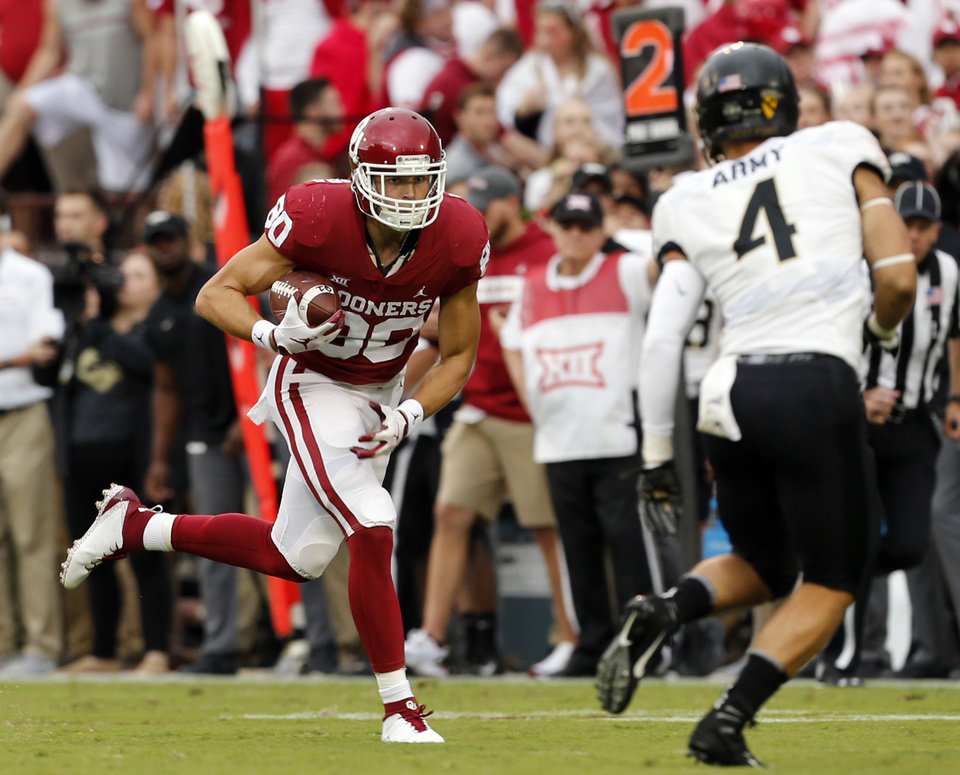 Photo - Oklahoma's Grant Calcaterra (80) catches a pass in front of Max Regan (4) during a college football game between the University of Oklahoma Sooners (OU) and the Army Black Knights at Gaylord Family-Oklahoma Memorial Stadium in Norman, Okla., on Saturday, Sept. 22, 2018. Photo by Steve Sisney, The Oklahoman