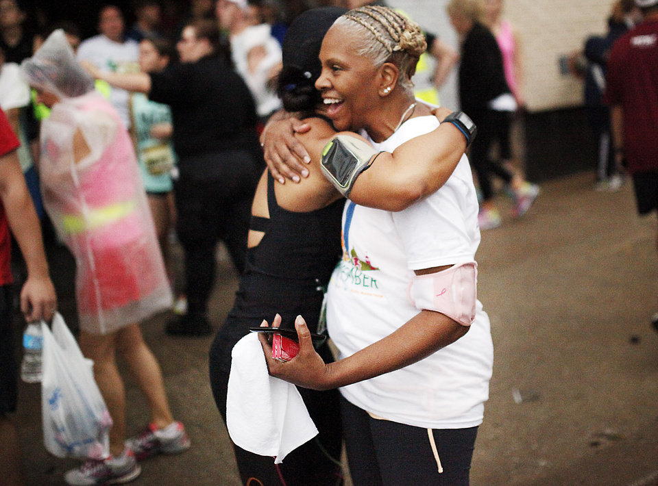 Photo - Devera Moore (right) hugs her sister Jackie Jackson (left) before Jackson runs her eighth marathon in the 14th Annual Oklahoma City Memorial Marathon in Oklahoma City, Sunday, April 27, 2014. The marathon was delayed over two hours beyond it's original start time of 6 a.m. Photo by KT King/The Oklahoman