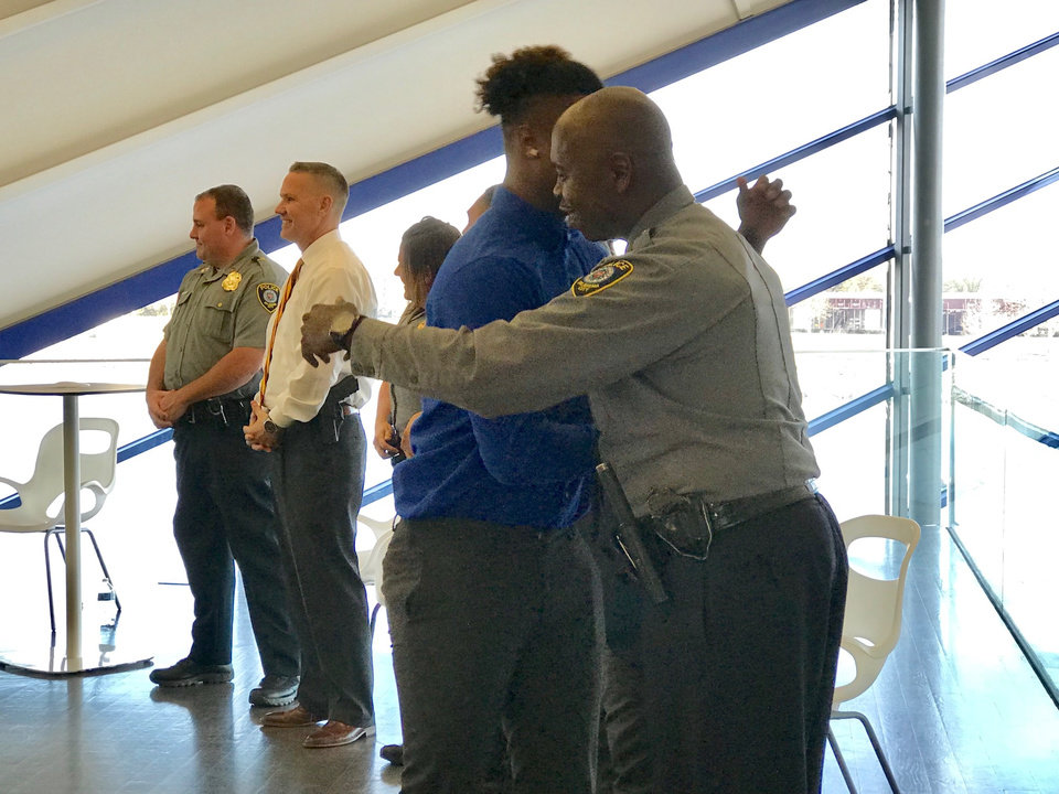 Photo -  Damian Byest, of Moore, hugs Oklahoma City police Sgt. Justin Echols at the recent graduation ceremony for the department's Juvenile Intervention Program held at the Devon Boathouse. [Photo by Carla Hinton, The Oklahoman]