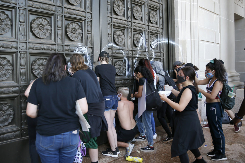 Photo - Protesters try to clean graffiti off the south doors of the state Capitol in Oklahoma City on Sunday, May 31, 2020. The Black Lives Matter protest was in response to the death of George Floyd. [Bryan Terry/The Oklahoman]