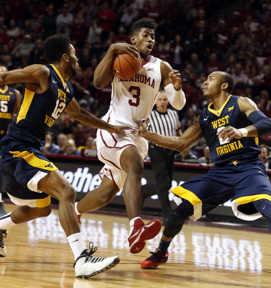 Photo - Oklahoma's Christian James (3) tries to go between West Virginia's Tarik Phillip (12) and Jevon Carter (2) as the University of Oklahoma Sooner (OU) men defeat the West Virginia Mountaineers (WV) 70-68 in NCAA, college basketball at The Lloyd Noble Center on Jan. 16, 2016 in Norman, Okla. Photo by Steve Sisney, The Oklahoman