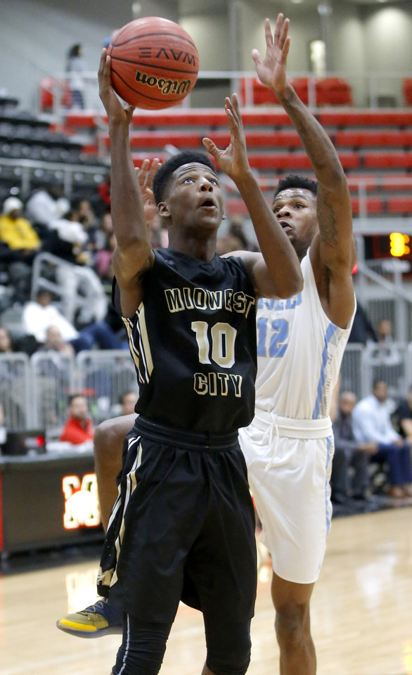 Photo - Midwest City's Kevin Overton goes to the basket past Lawton Eisenhower's Mark Berry during the Mustang Holiday Classic basketball tournament championship game between Midwest City and Eisenhower in Mustang, Okla. Saturday, Dec. 29, 2018. Photo by Bryan Terry, The Oklahoman