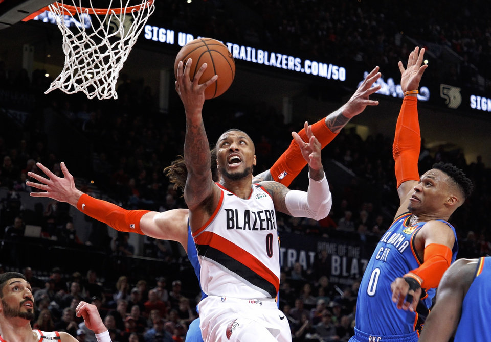 Photo - Portland Trail Blazers guard Damian Lillard, center, shoots as Oklahoma City Thunder guard Russell Westbrook, right, defends during the second half of Game 1 of a first-round NBA basketball playoff series in Portland, Ore., Sunday, April 14, 2019. (AP Photo/Steve Dipaola)