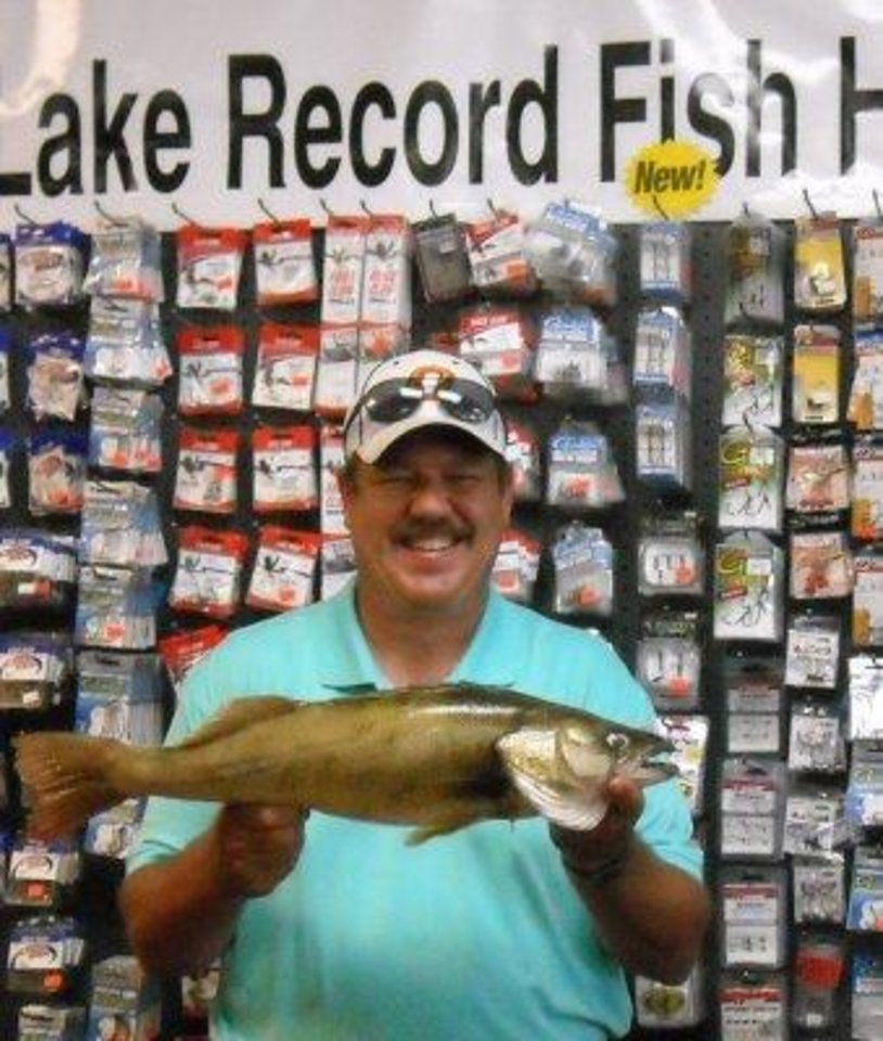 Photo -  Craig Lewis of Harrah poses at Lucky Lure Tackle in Oklahoma City with a 5.9-pound saugeye that he caught at El Reno Lake for the new lake record.