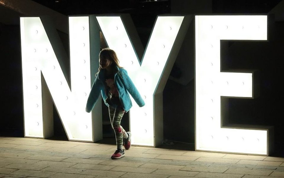 Photo - A child plays in front of the big NYE sign at Opening Night 2019 in Bicentennial Park in downtown Oklahoma City, Monday, December 31, 2018. [Doug Hoke/The Oklahoman Archives]