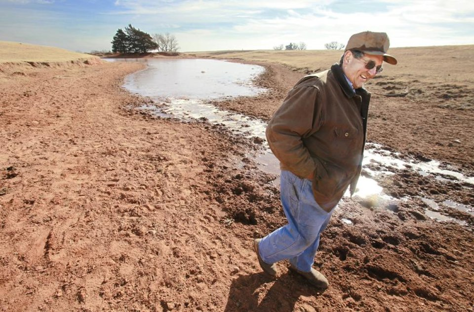 Photo -  John Pfeiffer, Pfeiffer Angus Farms, walks across a dried up part of one of his ponds on his ranch near Orlando, Wednesday, December 15, 2010. Photo by David McDaniel, The Oklahoman