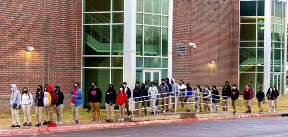Photo -  Students wait in line to return to class at U.S. Grant High School in Oklahoma City, Okla. on Tuesday, Nov. 10, 2020. Students in grades first through 12th return to Oklahoma City Public Schools for the first time since March. The school district will have students attend in-person classes twice a week in a hybrid A/B schedule. [Chris Landsberger/The Oklahoman]