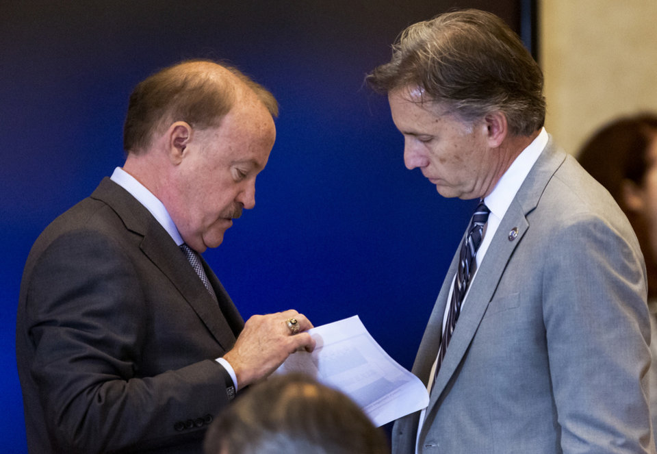 Photo - State's attorney Reggie Whitten, left, speaks with Attorney General Mike Hunter before the start of the opioid trial at the Cleveland County Courthouse in Norman, Okla. on Tuesday, May 28, 2019. The proceeding are the first public trial to emerge from roughly 2,000 U.S. lawsuits aimed at holding drug companies accountable for the nationÕs opioid crisis.  [Chris Landsberger/The Oklahoman]