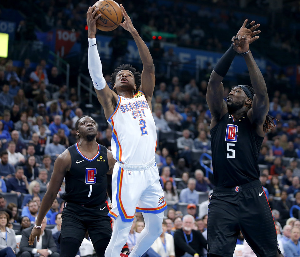 Photo - Oklahoma City's Shai Gilgeous-Alexander (2) goes to the basket between LA's Reggie Jackson (1) and Montrezl Harrell (5) during an NBA basketball game between the Oklahoma City Thunder and the Los Angeles Clippers at Chesapeake Energy Arena in Oklahoma City, Tuesday, March 3, 2020. [Bryan Terry/The Oklahoman]