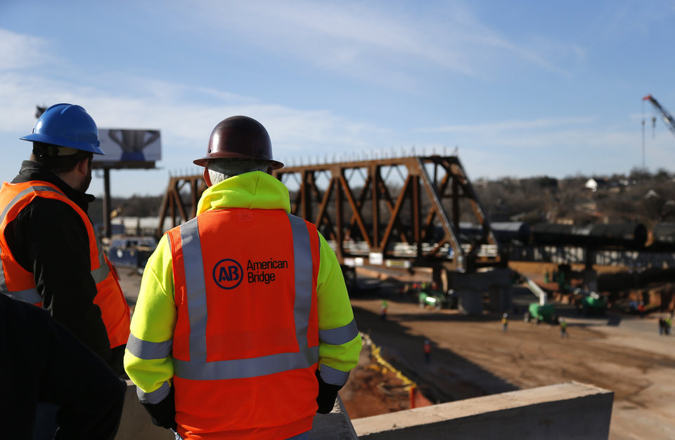 Photo -  People watch workers Saturday as they install the new railroad bridge over Interstate 235 in Oklahoma City. [Photo by Sarah Phipps, The Oklahoman]