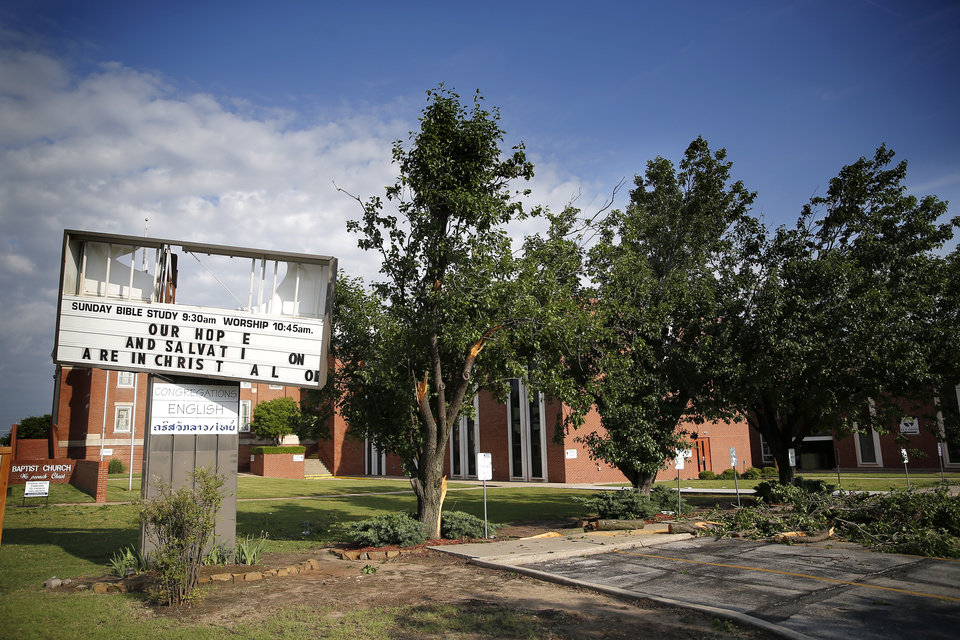 Photo - A sign at Trinity Baptist Church is pictured after an apparent tornado moved through the area in Oklahoma City, Sunday, May 26, 2019.  [Sarah Phipps/The Oklahoman]