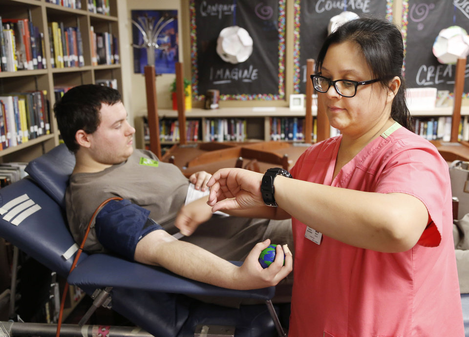 Photo -  Above: Centennial High School student Sebastian White prepares to have blood taken Jan. 15 by the Oklahoma Blood Institute's Mylene Poblete at the school in Oklahoma City.