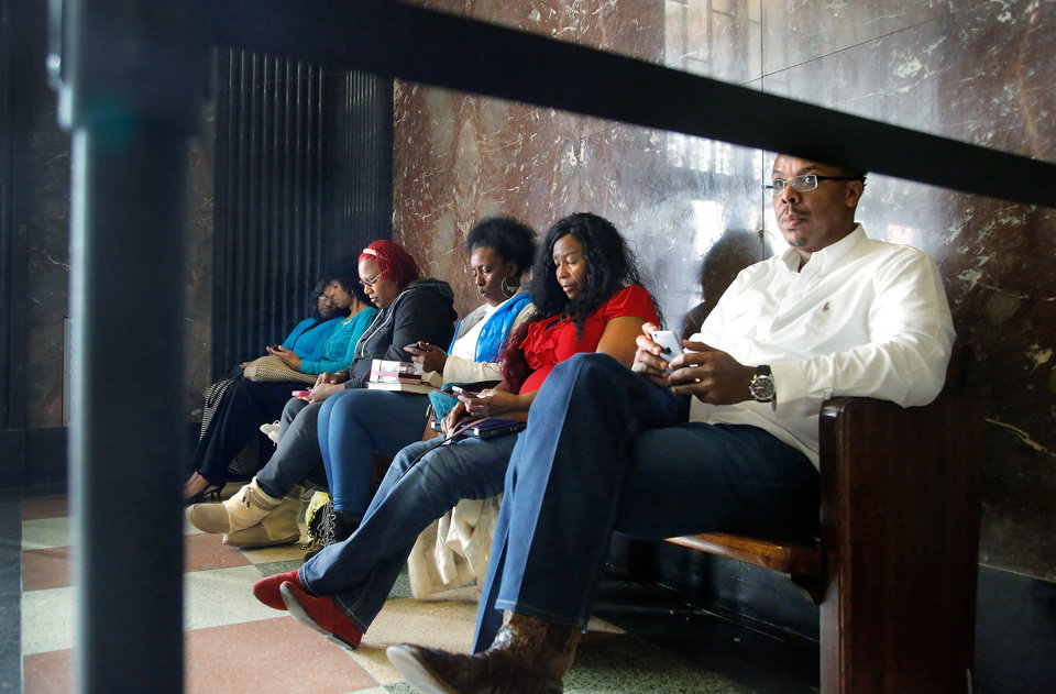 Photo - Robin Leake, third from right, and Rochelle Little, fourth from right,   join other supporters on a bench outside a courtroom on the second floor of the Oklahoma County Courthouse Thursday afternoon, Dec. 10, 2015, as the jury continues to deliberate in the sex crimes trial against  fired  police officer Daniel Holtzclaw.  They come to the courthouse to keep vigil through the deliberation process and to show support for the victims of the crimes. A jury of eight men and four women began deliberating Monday evening and so far have spent more than 40 hours discussing the case in seclusion at the Oklahoma County Courthouse. Holtzclaw, 29, is accused of sexual offenses against 13 black females between December 2013 and June 2014 while he was an Oklahoma City police officer. He was fired in January after being put on paid leave.He is charged with 36 counts, including six counts of first-degree rape. If convicted, he could spend the rest of his life in prison. He denies the allegations. Photo by Jim Beckel, The Oklahoman.