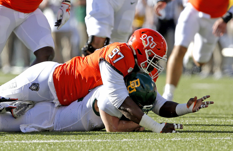 Photo - Oklahoma State's Amadou Fofana (97) tackles Baylor's Charlie Brewer (12) in the second quarter during the college football game between Oklahoma State University and Baylor at Boone Pickens Stadium in Stillwater, Okla., Saturday, Oct. 19, 2019. [Sarah Phipps/The Oklahoman]