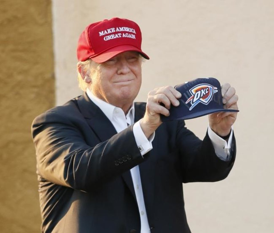 Photo -  Then-Republican presidential candidate Donald Trump holds up an Oklahoma City Thunder hat before tossing it into the audience before giving a speech during the Oklahoma State Fair on Sept. 25, 2015. [Photo by Nate Billings, The Oklahoman]