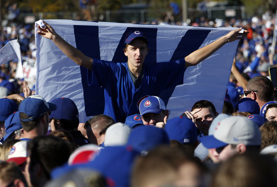 b3a4bbc73 A Chicago Cubs fan holds a flag as he celebrates before a rally in Grant  Park