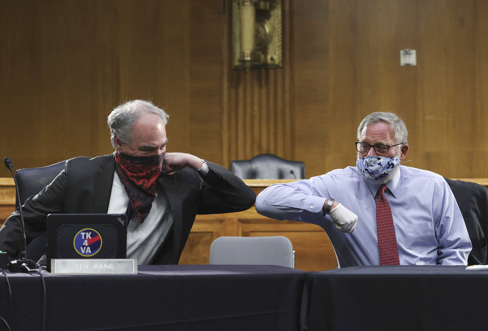 Photo -  Sen. Tim Kaine, D-Va., left, and Sen. Richard Burr, R-N.C., greet each other with an elbow bump before the Senate Committee for Health, Education, Labor, and Pensions hearing, Tuesday, May 12, 2020 on Capitol Hill in Washington. Dr. Anthony Fauci, director of the National Institute of Allergy and Infectious Diseases, is to testify before the committee.  (Win McNamee/Pool via AP)