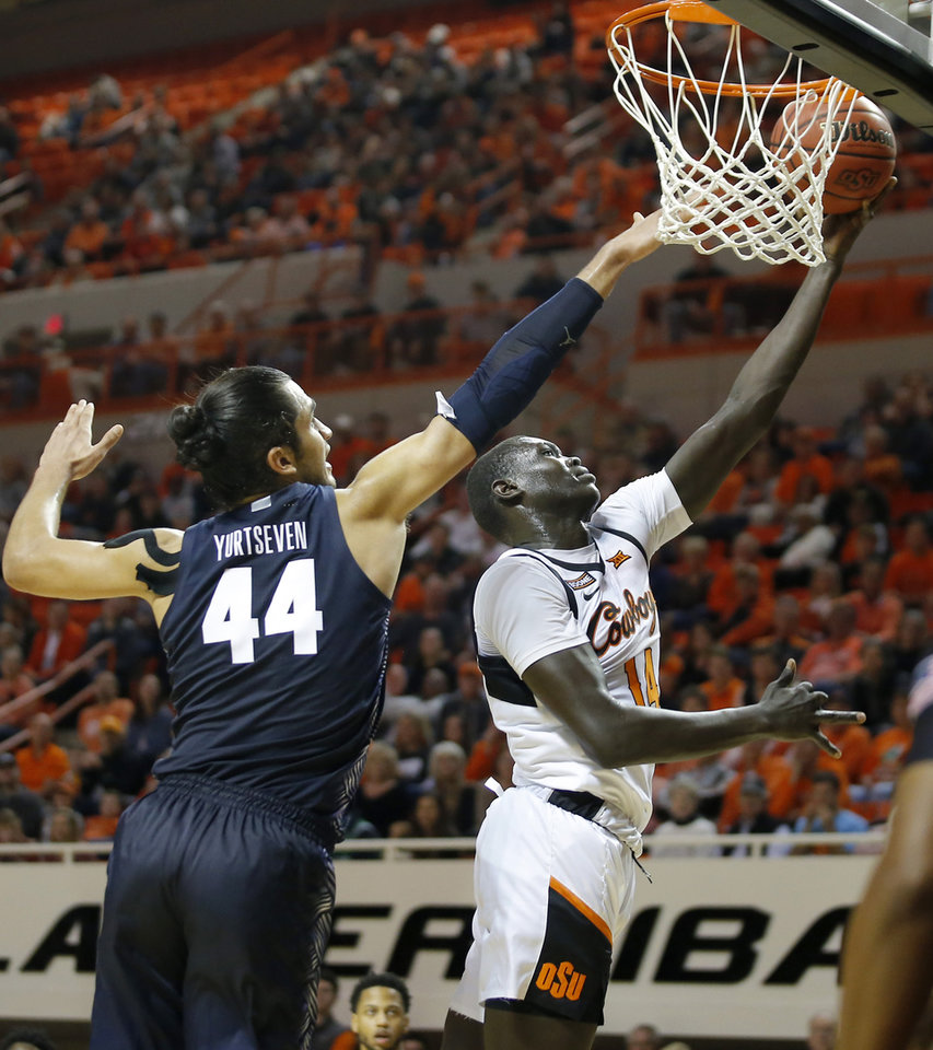 Photo - Oklahoma State's Yor Anei (14) goes past Georgetown's Omer Yurtseven (44) during a college basketball game between the Oklahoma State University Cowboys (OSU) and the Georgetown Hoyas at Gallagher-Iba Arena in Stillwater, Okla., Wednesday, Dec. 4, 2019. Georgetown won 84-71. [Bryan Terry/The Oklahoman]