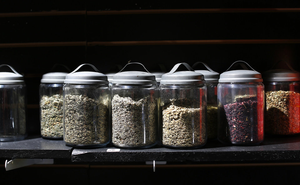 Photo - Herbs are stored in glass jars in McCloud's store in Spencer. Tamike McCloud is the owner of McCloudz's Pipes and Novelties in Norman, and he is still facing drug charges in that city in connection with police raids on his pipe store. Although defendants from the Friendly Market were acquitted in a similar case, and the rest of the charges were dismissed, McCloud is still facing up to 50 counts of possession of drug paraphernalia. McCloud is shown in his new store in Spencer, OKC BORO, which houses a glassblowing studio, and sells organic herbs as well as smoking accessories. Photo Taken on Tiesday, Dec. 26, 2017.  Photo by Jim Beckel, The Oklahoman