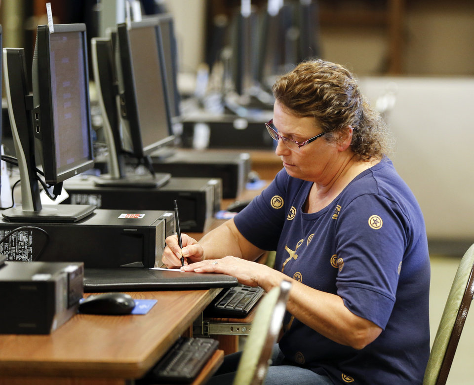 Photo -  Ann Hashman writes down information while using a computer to register with the OKJobMatch website at an OK Workforce center Monday in Oklahoma City.