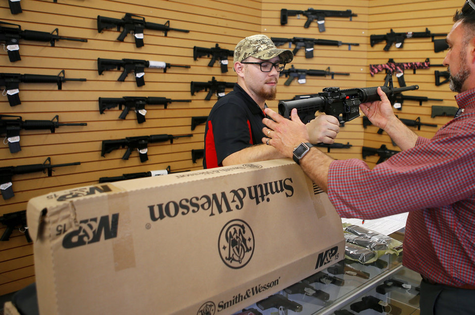 Photo -  Bryce Wilson helps Brian, no last name given, purchase a semi-automatic rifle at Big Boys Guns & Ammo in Oklahoma City. Photo by Bryan Terry, The Oklahoman