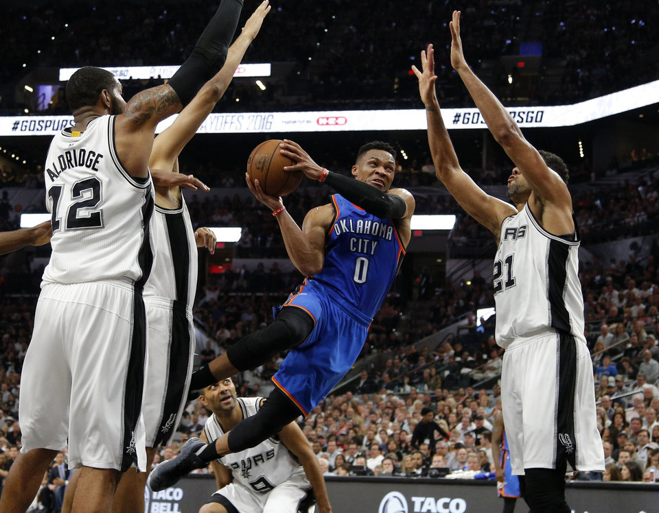 Photo - Oklahoma City's Russell Westbrook (0) is fouled as he goes to the basket between San Antonio's LaMarcus Aldridge (12) and Tim Duncan (21) during Game 5 of the second-round series between the Oklahoma City Thunder and the San Antonio Spurs in the NBA playoffs at the AT&T Center in San Antonio, Tuesday, May 10, 2016. Photo by Bryan Terry, The Oklahoman