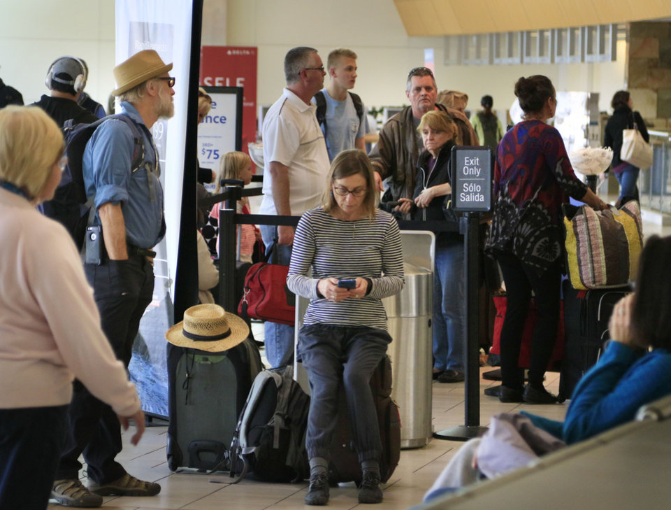 Photo -  Travelers line up Monday at the Southwest Airlines counter at Will Rogers World Airport in Oklahoma City. [Photo by Paul Hellstern, The Oklahoman]