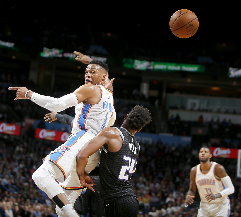 Photo - Oklahoma City's Russell Westbrook (0) passes over Sacramento's Buddy Hield (24) during an NBA basketball game between the Oklahoma City Thunder and the Sacramento Kings at Chesapeake Energy Arena in Oklahoma City, Saturday, Feb. 23, 2019. Photo by Bryan Terry, The Oklahoman
