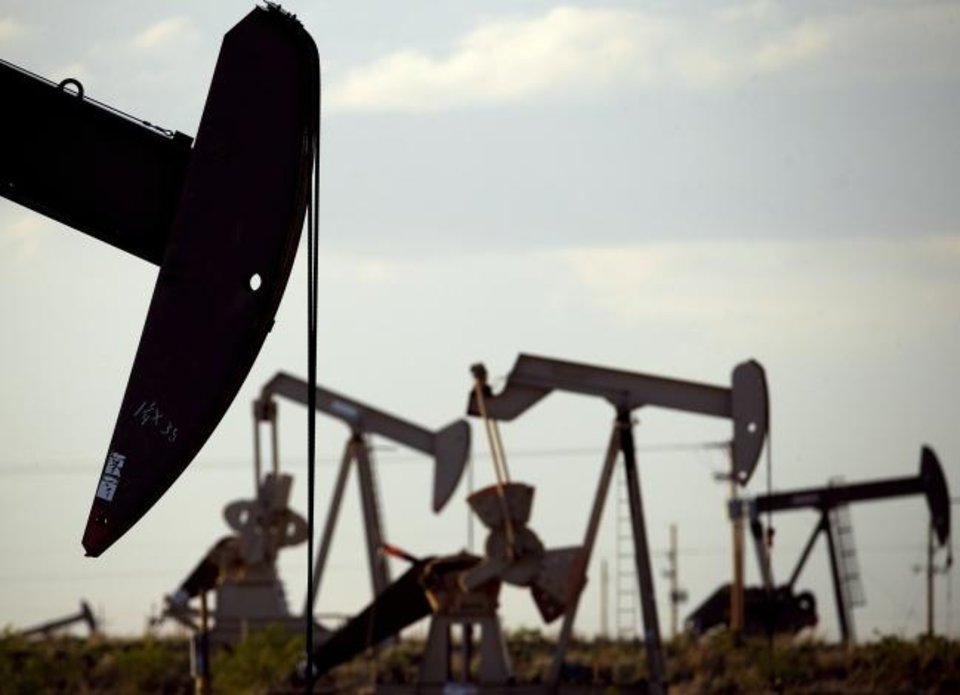Photo -  Pumpjacks work in a field near Lovington, N.M. [AP PHOTO]