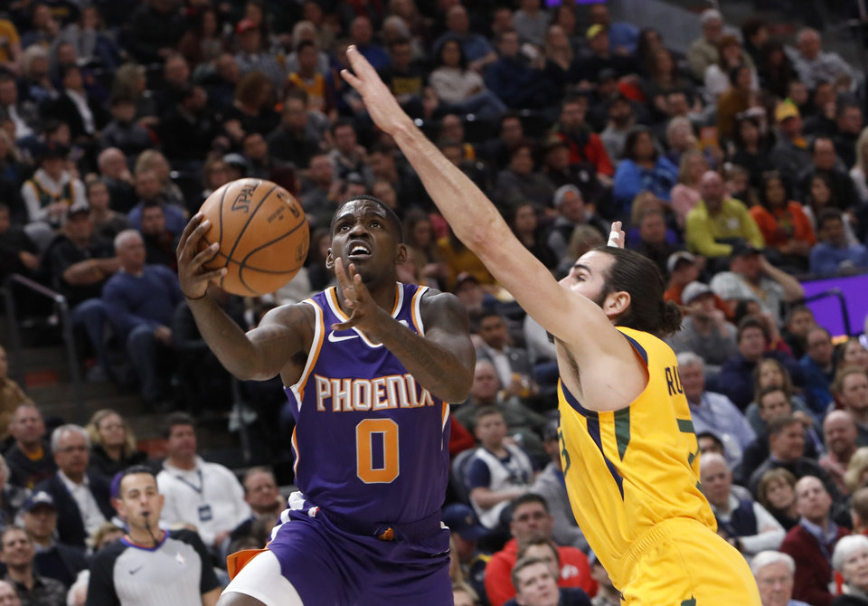 Photo - Phoenix Suns' Jawun Evans (0) attempts a layup as Utah Jazz's Ricky Rubio, right, defends in the first half of an NBA basketball game on Wednesday, Feb. 6, 2019, in Salt Lake City. (AP Photo/Kim Raff)