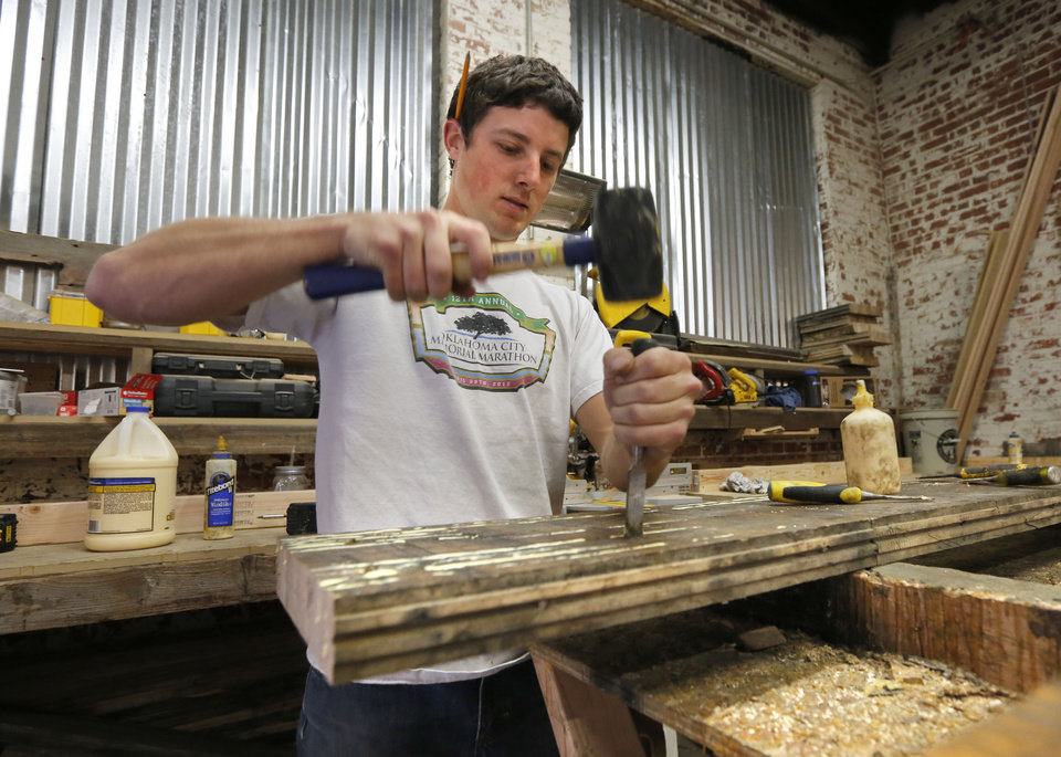 Photo - Preston Bullard separates old wood joints in order to re-glue them for a table top at