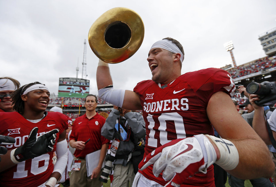Photo - Oklahoma's Blake Bell (10) celebrates with the Golden Hat Trophy after  the Red River Showdown college football game between the University of Oklahoma Sooners (OU) and the University of Texas Longhorns (UT) at the Cotton Bowl in Dallas on Saturday, Oct. 11, 2014. 
