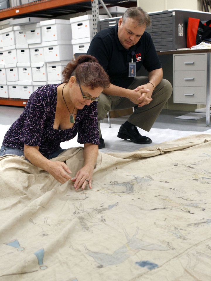 Photo - Textile conservator Anne Murray and curator Matt Reed work to preservea nearly 100-year-old tepee at the Oklahoma History Center. Photo by Paul Hellstern, The Oklahoman  PAUL HELLSTERN - Oklahoman