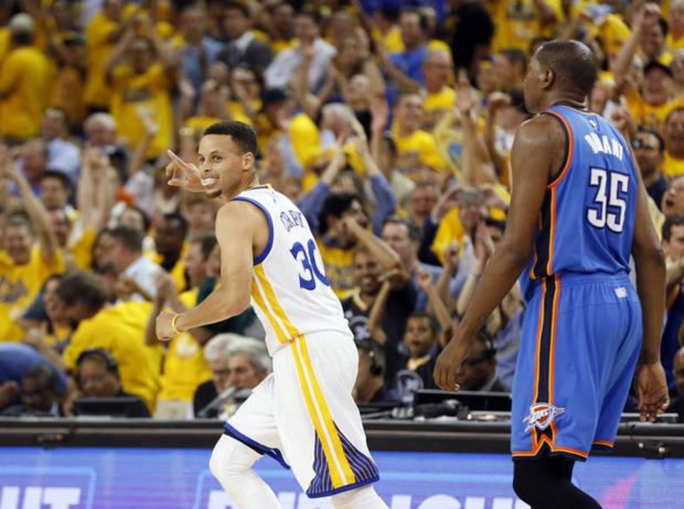 Photo - Golden State's Stephen Curry (30) celebrates after hitting a three-point shot as he runs back on defense in front of Oklahoma City's Kevin Durant (35) in the third quarter during Game 2 of the Western Conference finals in the NBA playoffs between the Oklahoma City Thunder and the Golden State Warriors at Oracle Arena in Oakland, Calif., Wednesday, May 18, 2016. Golden State won 118-91. Photo by Nate Billings, The Oklahoman