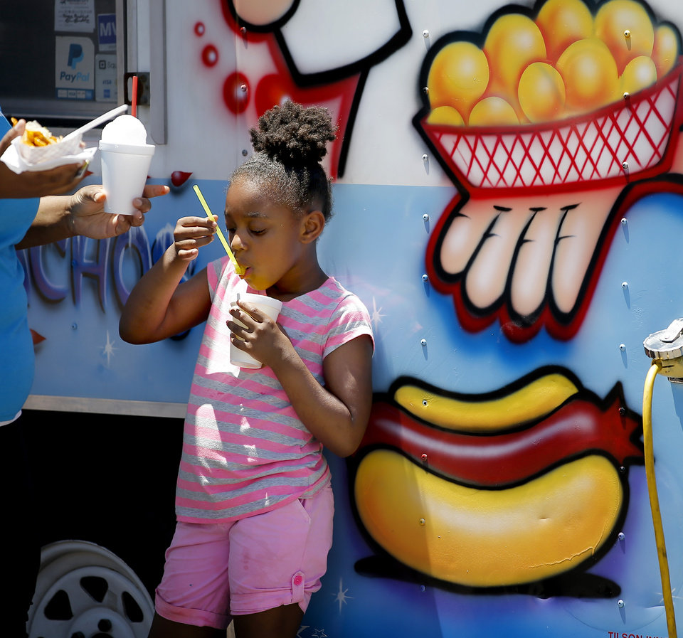 Photo - Myhonna Jackson, 7, eats a snow cone during the oNE OKC annual street festival hosted Northeast OKC Renaissance Inc. in Oklahoma City, Saturday, June 8, 2019. [Bryan Terry/The Oklahoman]