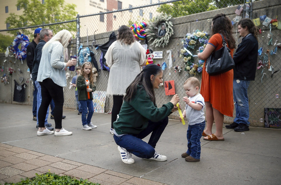 Photo - Aren Almon, center kneeling, and nephew Brixten Clymer, 22 months, put a wand in a tube while blowing bubbles near other members of the Almon family at the fence outside of the Oklahoma City National Memorial and Museum on the 25th anniversary of the bombing of the Alfred P. Murrah Federal Building, in Oklahoma City, Sunday, April 19, 2020. Aren Almon's one-year-old daughter Baylee Almon died in the bombing. The memorial remains closed and did not hold a live remembrance ceremony because of the coronavirus pandemic. [Nate Billings/The Oklahoman]