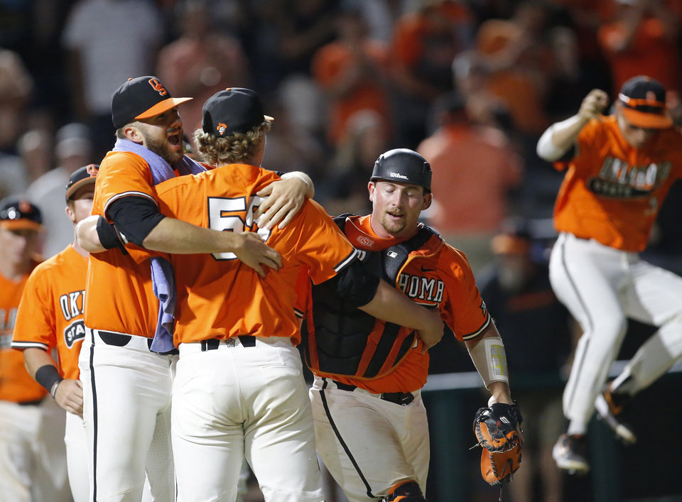 Photo - Oklahoma State's Joe Lienhard (46), Peyton Battenfield (55) and Colin Simpson (24) celebrates the Cowboys' win over UConn during the Oklahoma City Regional NCAA baseball game between Oklahoma State University (OSU) and UConn at Chickasaw Bricktown Ballpark in Oklahoma City,  Monday, June 3, 2019. [Sarah Phipps/The Oklahoman]