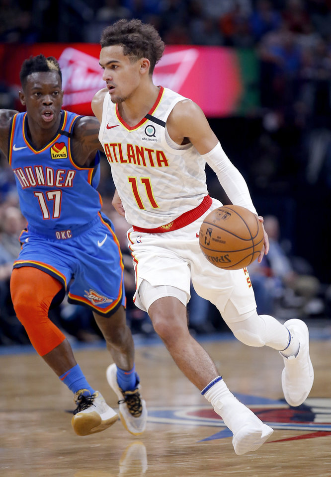 Photo - Atlanta's Trae Young (11) drives up court at Oklahoma City's Dennis Schroder (17) defends during the NBA basketball game between the Oklahoma City Thunder and the Atlanta Hawks at the Chesapeake Energy Arena in Oklahoma City,Friday, Jan. 24, 2020.  [Sarah Phipps/The Oklahoman]