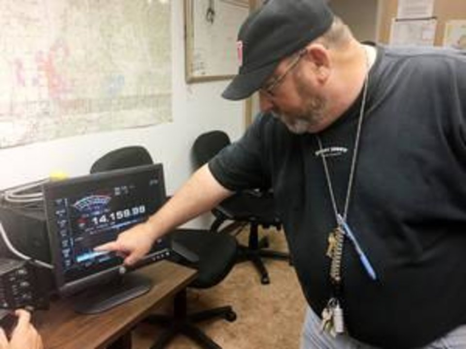 Photo -  Clay Mayrose, 57, of Guthrie, explains how to operate the radio equipment at the Edmond Downtown Community Center. [PHOTO BY NICK SARDIS, THE OKLAHOMAN]